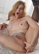 Transsexual MILF fingering her asshole in bed