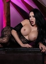 Watch busty Kimberlee stroke her massive thick cock while wearing a sexy catsuit